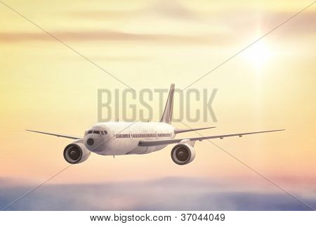 A commercial Jet flying high above the clouds into the sunset.