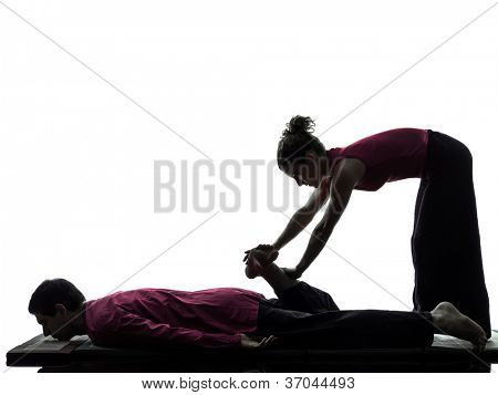 one man and woman perfoming feet legs thai massage in silhouette studio on white background