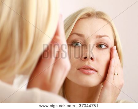 Woman caring of her beautiful skin on the face standing near mirror