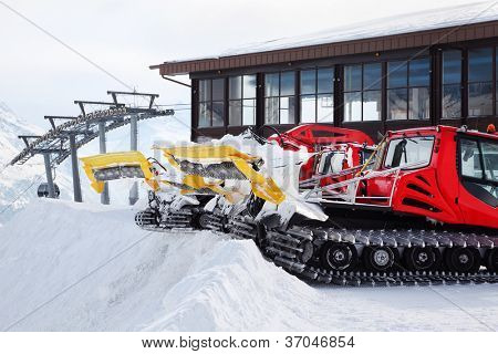 Two red machines for skiing slope preparations in Austrian Alps.
