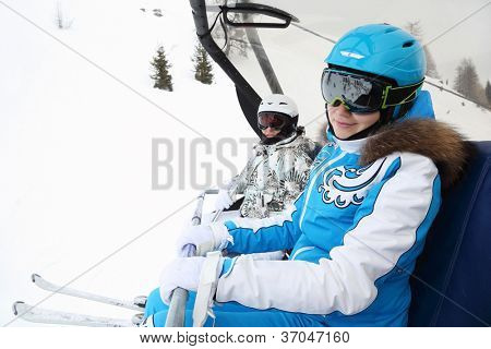 Two smiling female skiers in special clothing ride on cable car in mountains. Focus on right woman.