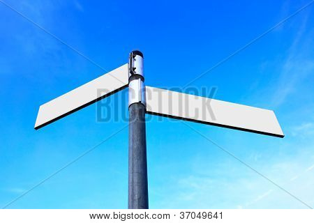 Blank white road signs over blue sky