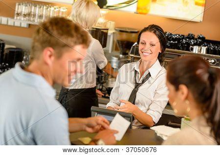 Paar Rechnung an Café-Kasse lächelnd Kellnerin Bar bezahlen