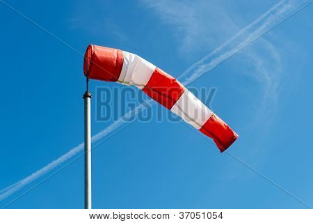 red and white windsock on pole