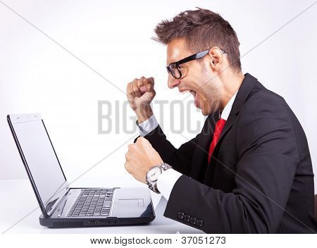 side view of a happy arm rising winning business man working on his laptop computer at his desk