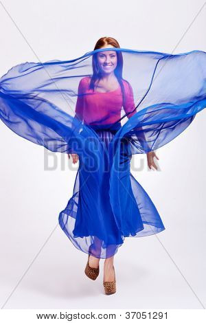 young woman throwing her dress up in the air and smiling to the camera