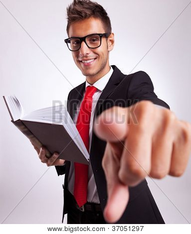 young business man reading a book and choosing you to take his example