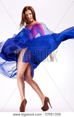 young sexy woman model in a fluttering dress screaming while looking at the camera