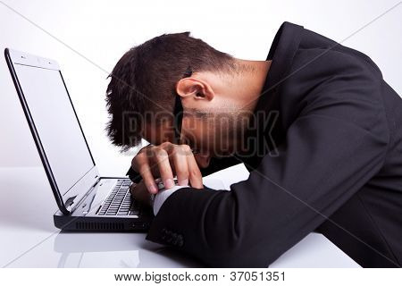 Tired business man with head and hands down on laptop
