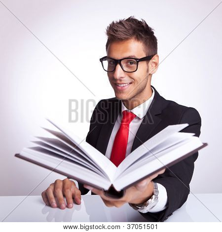 business man wearing glasses offering his book to you to read and smile