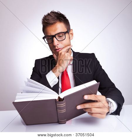 intrigued business man reading a book and wondering what will happen next
