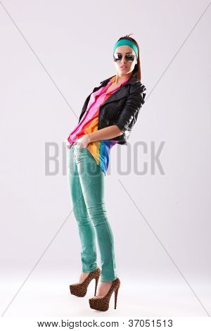 side view of a casual fashion woman in leather jacket and sunglasses standing with her hands in her pockets