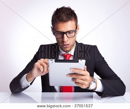 amazed business man wearing glasses selecting something on his electronic pad