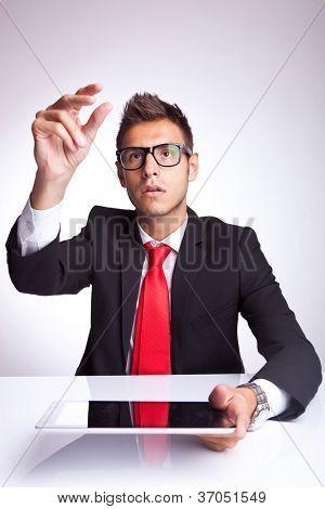 junger Geschäftsmann Kommissionierung etwas imaginären oben sein Touchscreen-Pad auf graue Studio-Hintergrund