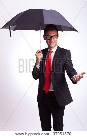 young business man reaching and checking with his hand if it rains