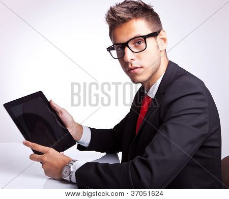 side view of a young business man holding his tablet pad and looking to the camera