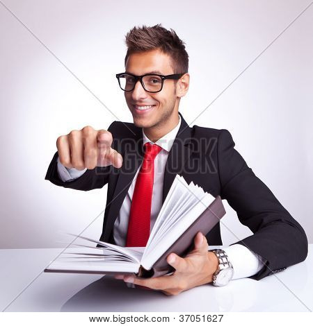 young business man at his desk reading a book and choosing you to read it too