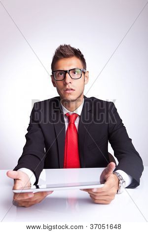 amazed young business man looking at something imaginary above his pad , sitting at his desk