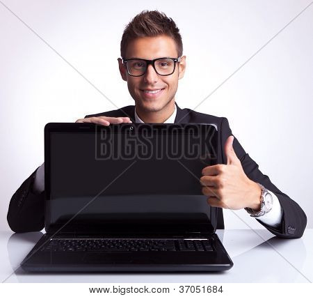 business sitting at desk showing you a laptop computer and the thumbs up desture