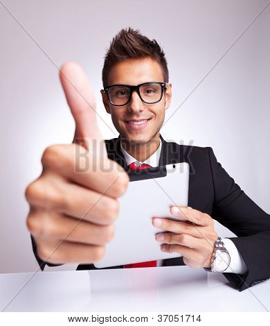 young business man making the ok thumbs up gesture while readin on his tablet pad