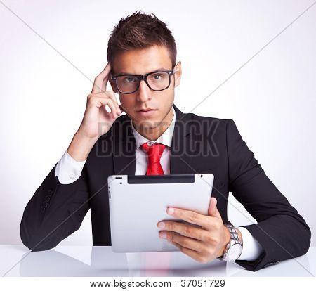 hombre de negocios seria y profunda con una almohadilla de tableta electrónica y mirando a la cámara