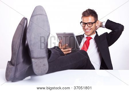 relaxed business man wearing glasses  sitting at his desk and reading something on his pad and smiling