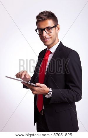 young business man holding a touch screen pad and looking to the camera, smiling