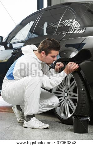 auto mechanic worker painting element car at automobile repair and renew service station shop by power buffer machine