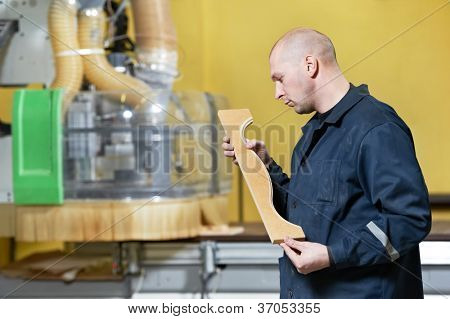 mechanical technician worker examining wood furniture part after milling machine center at manufacture workshop