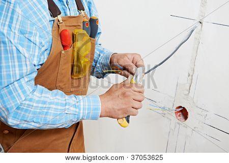 Primer plano de las manos de trabajador electricista en cable de cableado y el interruptor o enchufe de toma de corriente de pared en