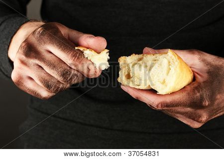 homeless man holding a white bread, close-up