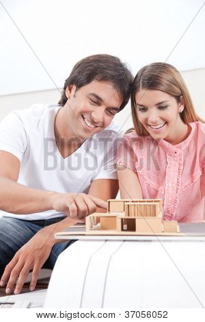 Happy young couple looking at house model .
