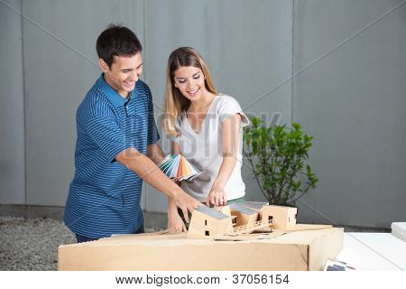 Happy young couple selecting colors from swatches for model house