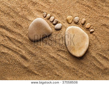 two traces of the feet made of a pebble stones  on the sea sand desert