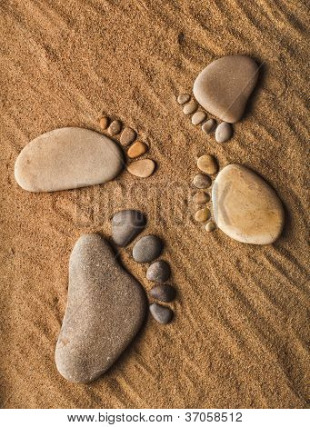 traces of the feet made of a pebble stones  on the sea sand