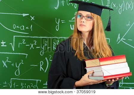 Graduating student girl in an academic gown standing with books at the classroom.