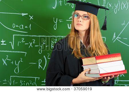 Studium Student Mädchen in einer akademischen Kleid stehend mit Bücher in der Schule.