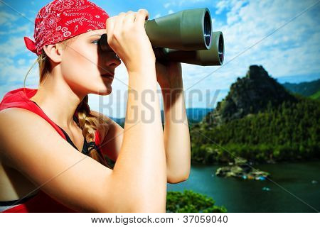 Young woman tourist is looking through the binoculars at the top of a mountain.