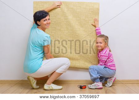 Happy woman and her daughter with wallpaper roll