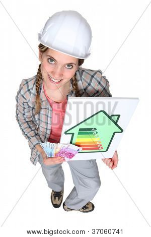 Tradeswoman holding an energy efficiency rating sign and a wad of money