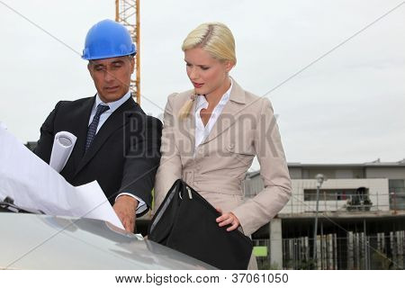 Architect and assistant visiting construction site