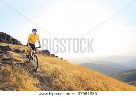 A young male riding a mountain bike on a sunset, Macedonia