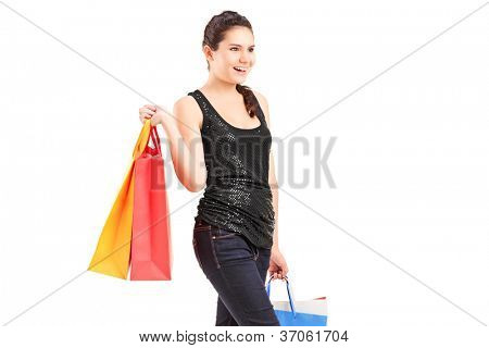 A young female holding shopping bags and walking, isolated on white background