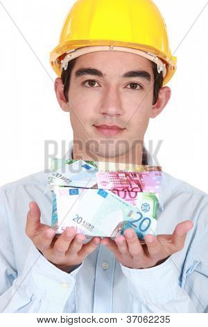 Young builder holding a house made of money