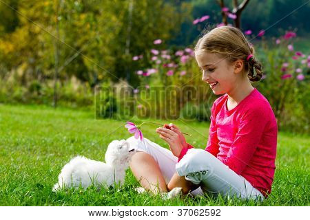 Happy childhood - lovely girl playing with cute puppy in the garden