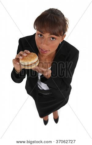 Businesswoman eating a hamburger