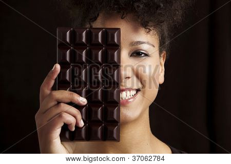 Beautiful african woman holding a huge dark chocolate bar
