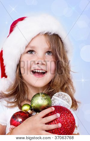Portrait of a laughing preschool girl in Santa hat holding Christmas decoration in hands