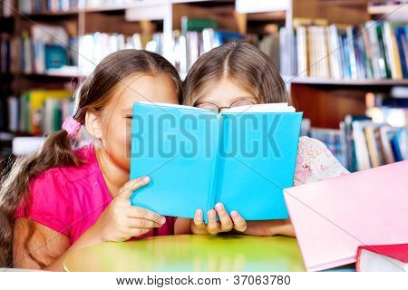 Two girls reading a book in a library