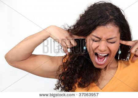 An African American woman plugging her ears.